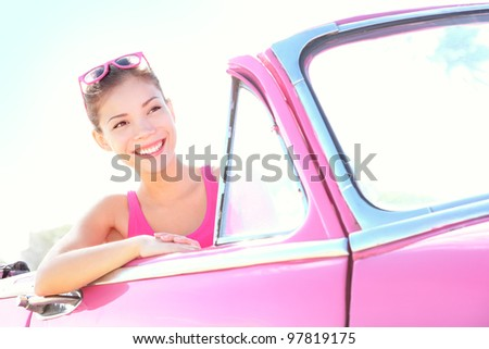 Woman driving vintage car. Retro style image of happy smiling young woman in old pink car going on road trip on sunny spring or summer day. Beautiful multiracial Caucasian / Asian in Havana, Cuba.