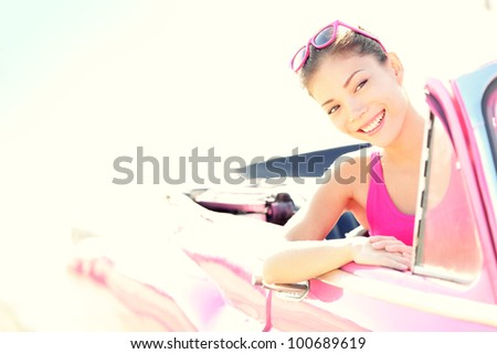 Woman driving vintage retro convertible car in pink. Retro style portrait of young beautiful happy smiling asian woman driver.