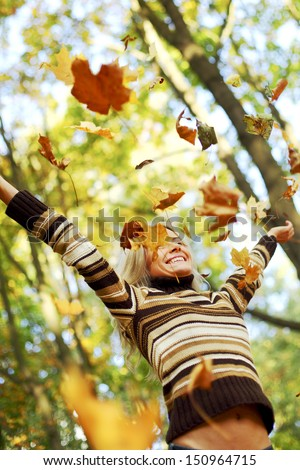 woman drop up leaves in autumn park - stock photo