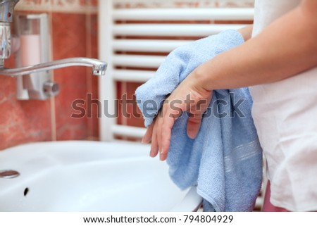 Woman dry hands with towel in bathroom