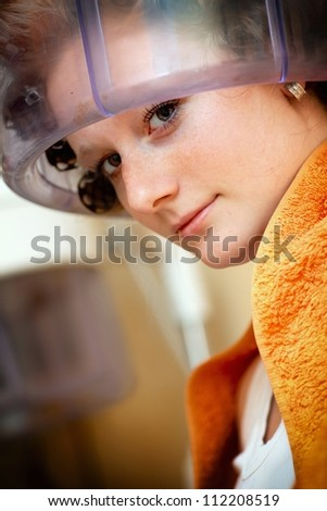 Woman drying hair at the hairdresser - stock photo