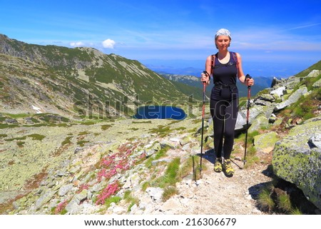 Woman during hiking trip on sunny mountain decorated with red flowers