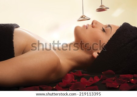 Woman during sound therapy in spa. Isolated with work path. - stock photo