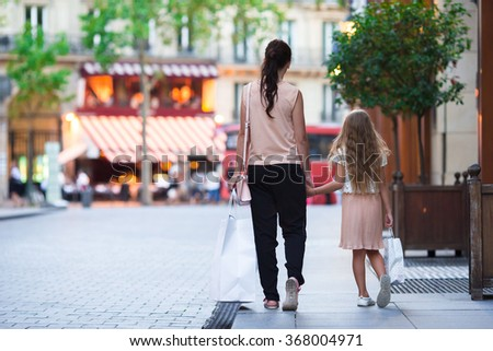 Woman during the shopping with the little adorable girl in Paris outdoors - stock photo