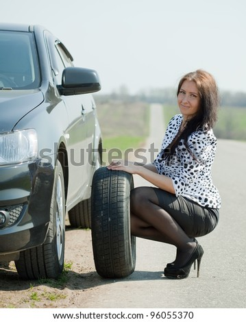 woman during the wheel changing at road - stock photo