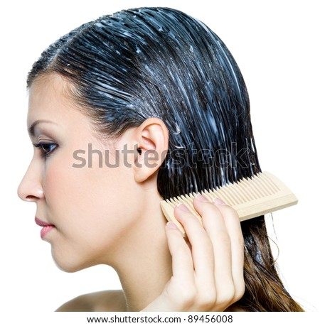 woman dyeing hairs and combing them  with comb - isolated on white - stock photo