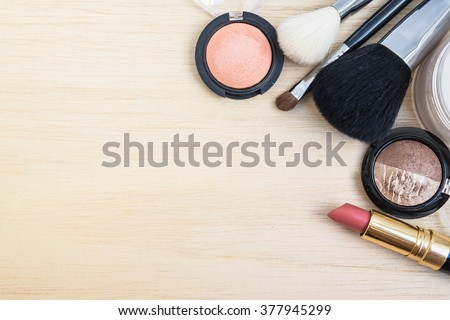 Woman earth tone cosmetics  (make-up) - eyeshadow, brush on, lipstick, powder, brush. Top view with space for text. - stock photo