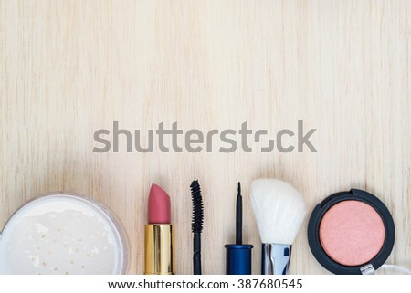 Woman earth tone cosmetics  (makeup) - mascara, eye liner, brush on, lipstick, powder, brush on wood background. Top view with space for text. - stock photo