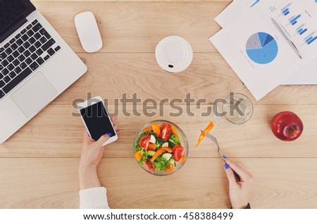 Woman eat business lunch at working place. Businesswoman's hands with fork and mobile on wooden desk in office. Healthy diet food, vegetable salad with apple near laptop and papers. Top view, flat lay - stock photo