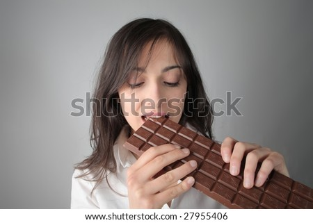 woman eating a bar of chocolate - stock photo