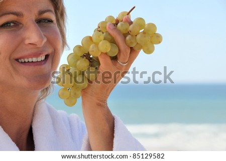 Woman eating a bunch of grapes by the sea - stock photo