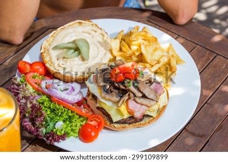 Woman eating a cheese burger at the summer lounge bar - stock photo
