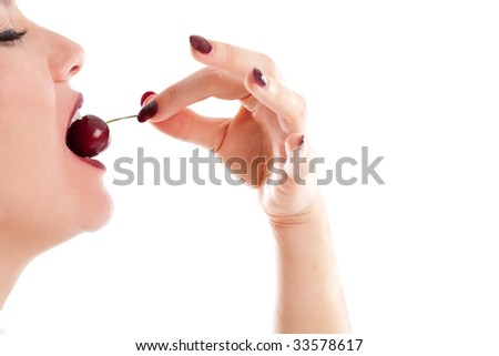 Woman eating a cherry on white background - stock photo