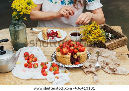 Woman eating a delicious home-made cake with aisheny and stuffed strawberries for dessert. Summer Styled dinner table. Coffee to the cake. sitting at the rustic dining table - stock photo