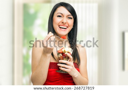 Woman eating a fruit cocktail - stock photo