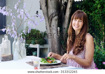 Woman eating a healthy salad lunch in a outdoor garden cafe alfresco style  - stock photo