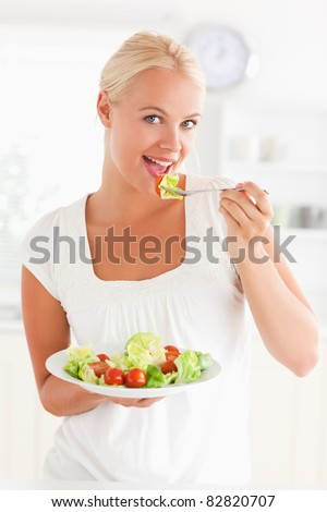 Woman eating a salad in her kitchen - stock photo