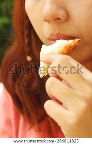 Woman eating a sandwich with ham and cheese.