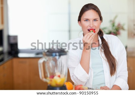 Woman eating a strawberry in her kitchen - stock photo