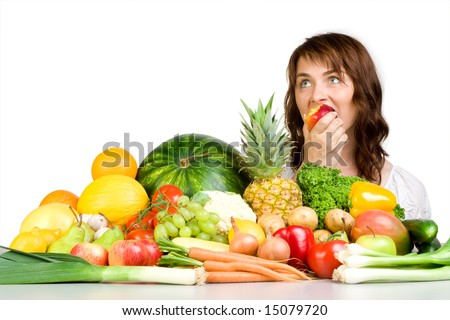 Woman eating an apple with a table full of produce before her. - stock photo