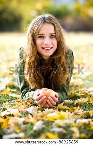 Woman eating apple outdoors in autumn - stock photo