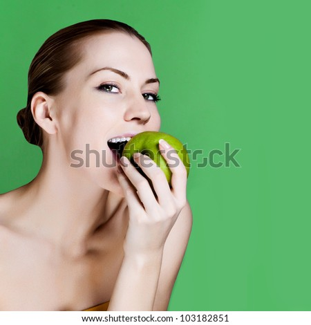 Woman eating apple smiling on green background. Healthy eating candid woman.