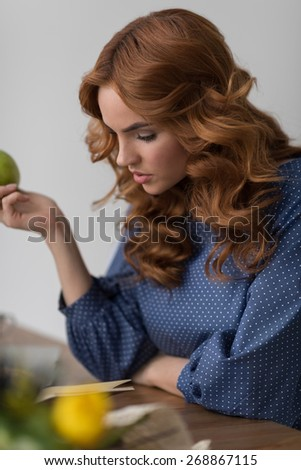 Woman eating apple while working at home or office with notebook and laptop - stock photo