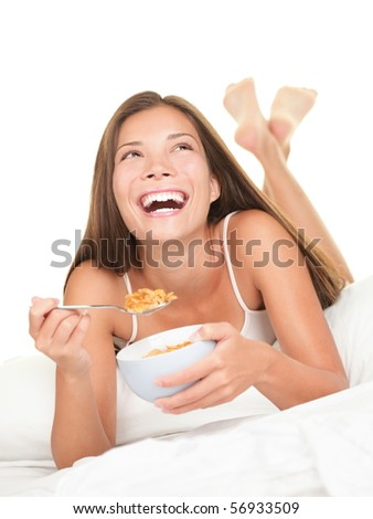 Woman eating breakfast in bed. Happy woman enjoying cornflakes cereals in the bed in the morning. Beautiful mixed race Chinese Asian / Caucasian female model lying in bed isolated on white background