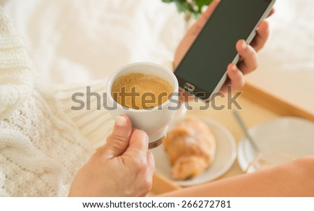 Woman eating breakfast in bed while looking at your mobile phone - stock photo