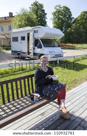 Woman eating breakfast outdoors in fron of her camping car. She has a pair of binoculars on her knees. - stock photo