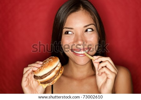 Woman eating burger and fries smiling. Beautiful mixed race asian caucasian female model on red background. - stock photo