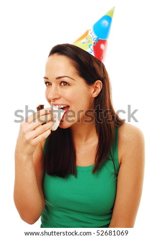 Woman eating cake wearing party hat - stock photo