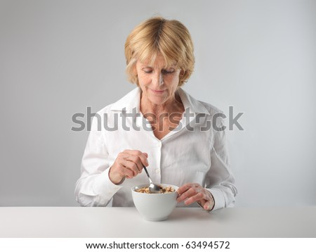 Woman eating cereals - stock photo