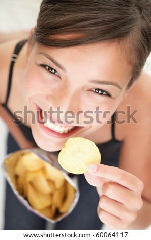 Woman eating chips. Beautiful young woman eating potato chips / crisps. - stock photo