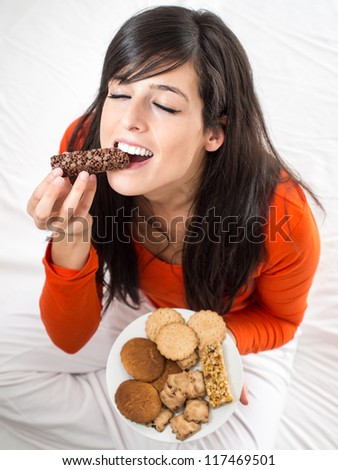 Woman eating chocolate bar. Hungry girl biting delicious  snack sitting on white bed indoor. Breaking diet concept.