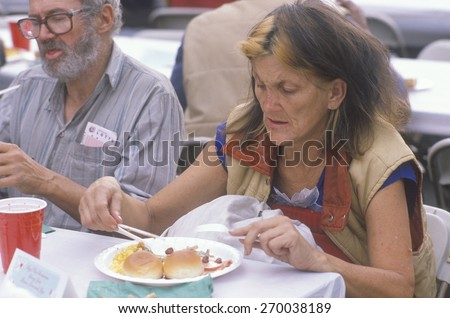 Woman eating Christmas dinner at homeless shelter, Los Angeles, California - stock photo