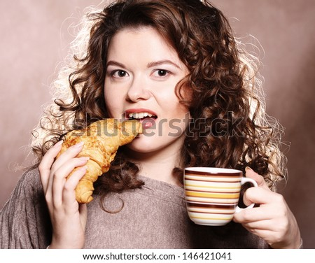 Woman eating cookie and drinking coffee.