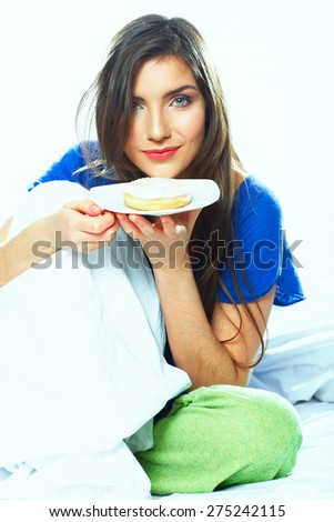 Woman eating donut. Young female model portrait . - stock photo