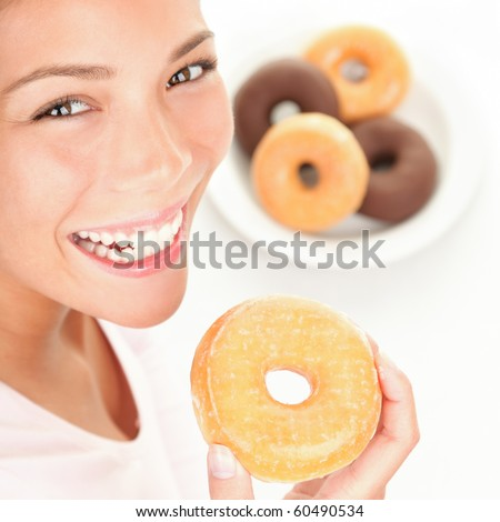 Woman eating donuts. Young woman smiling eating a donut with a plate of donuts in the background.