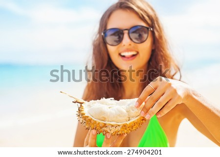 woman eating durian on a beach (focus on her hands) - stock photo