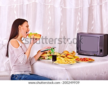 Woman eating fast food and watching TV. Isolated. - stock photo