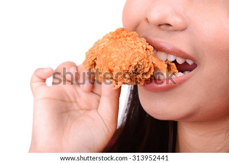 Woman eating fried chicken, on white background - stock photo