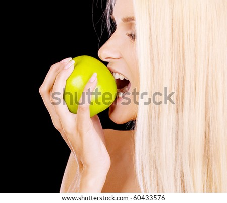 Woman eating green apple, isolated on black background. - stock photo