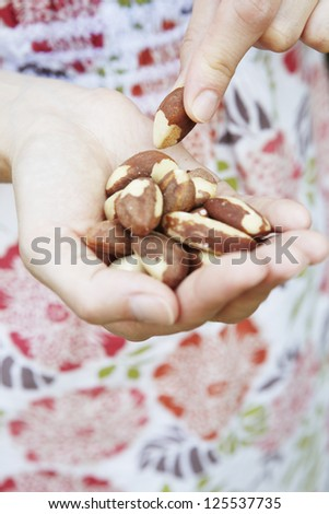 Woman Eating Handful Of Brazil Nuts - stock photo