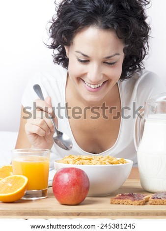 Woman eating healthy breakfast with cereals at morning on bed looking her food. Happy beautiful woman having breakfast of milk, cereals, orange juice, toasts and fruit. Concept of nutrition and diet. - stock photo