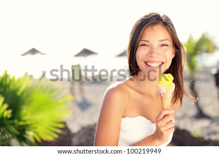 Woman eating ice cream outside on summer vacation in holiday beach resort. Happy mixed race girl in her twenties - stock photo