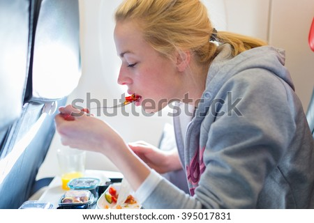 Woman eating meal on commercial airplane.  - stock photo