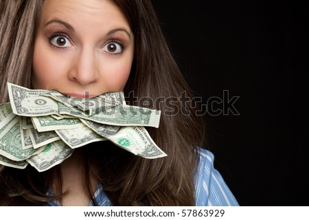 Woman eating money in mouth - stock photo