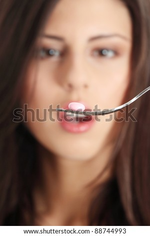 Woman eating nutritional supplement - pill on fork. Focus on fork