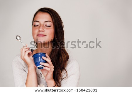 Woman Eating out of Small Dish - stock photo